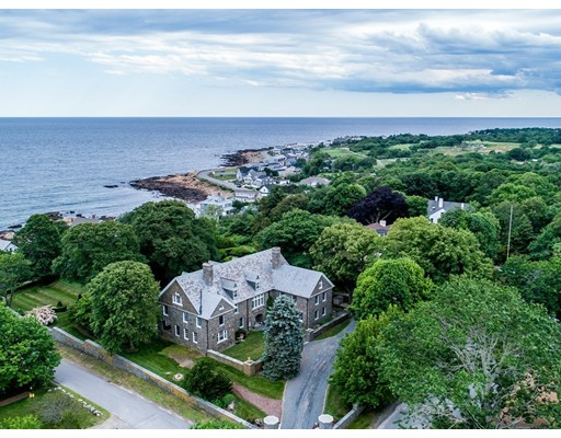 """Located in one of the most desirable locations on Gloucester's Back Shore, this visually arresting estate with stone architecture, ocean views, and impeccable lawns rolling down to the sea presents a rare blend of timeless luxury and 21st century convenience. Steps to Good Harbor Beach and Bass Rocks Golf Club, this spectacular home has been meticulously renovated to incorporate the modern amenities and systems that allow for unfettered enjoyment of life in one of New England's finest seaside communities. The home has the iconic features of a turn-of-the-century great house—a grand staircase, soaring floor-to-ceiling windows, long airy passageways, a solid stone """"tea room""""  overlooking the sea and original design elements such as wood-paneled walls, ornate mantels & fireplaces, stone and hardwood floors, and custom built-ins and closets. Its luxurious interiors offer constant views of sea and sky, while its tiered design and versatile floor plan facilitate a variety of living options."""