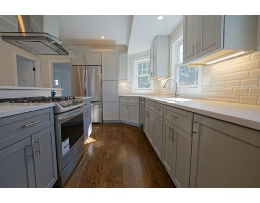 STRIKING 2018 RENOVATION! Located just a short walk to Roslindale Village and Commuter Train.  This 1635 sq. ft. condominium on two levels of living feels like a town home.  Complete gut renovation inside and out.  All new systems: wiring, plumbing, on demand H20 & HVAC.  Architect designed with open concept and dark wood floors throughout.  The kitchen features gray cabinetry, quartz counters, five burner gas stove, glass hood vent, subway tile backsplash and a breakfast bar.  Bathrooms include designer tile work, quartz vanities and glass shower doors.  600+ sq. ft. 3rd level family room w/ french doors, beamed ceiling and deck with treetop views, plus 2nd master bedroom with ensuite bath and walk-in closet. Off-street parking for one car.
