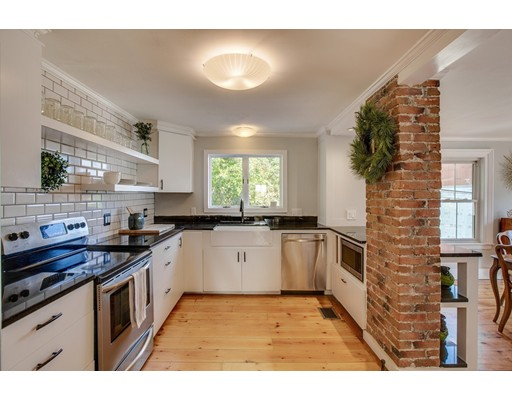 This superbly charming home has been thoughtfully updated w/ modern finishes while maintaining warm period details.  Refinished wide pine floors, crown molding, distinctive Corbels, exposed brick, blend w/ granite counters, stainless steel appliances, recessed lighting, and a soft color palette. The updated kitchen w/ farmers sink opens to the sun-washed dining room and is the perfect place to host family and friends. The 1st floor bath has been artfully renovated w/ tiled bath and mosaic insert. The master bedroom w/ walk-in closet provides ample space for the serious fashionista.  A 2nd bedroom has a built-in custom desk made of reclaimed wood from an Exeter, NH barn; how charming!  Renovation of 2nd floor bath w/ laundry is nearly complete - all new.  Tremendous expansion potential w/ walk-up attic.  20x12 balcony overlooks a private yard w/ unobstructed river views. Spacious shed/workshop.  Easy commuter access to 95/495.  Amesbury, a thriving restaurant, art & business community!