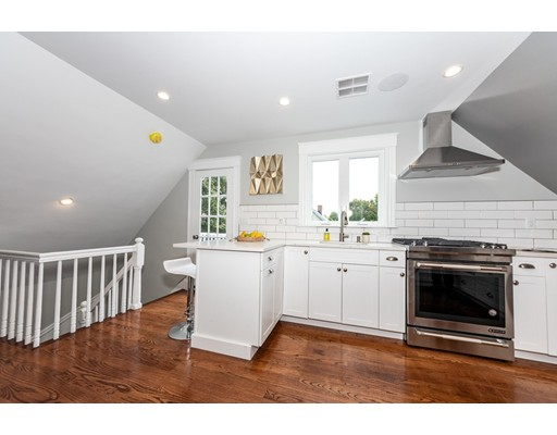 STUNNING BRAND NEW RENOVATION of a top floor tree-top retreat! This central Roslindale location is perfectly located between Roslindale Village & West Roxbury Center! This condo is only minutes to the Bellevue commuter train station which offers an ideal commute inbound to Back Bay & South Stations! Unit #3 offers a dynamic and open concept floor plan which is perfect for entertaining and everyday living! Your wish list is complete with a Chef inspired kitchen with custom shaker soft close cabinets, quartz countertops, subway tile backsplash, high-end Jenn-Air Appliances & 5 burner gas stove!  Fine details include: lavish wood work, wainscoting, multi room sound system, tall ceilings, recessed LED lighting, Harvey windows, wood floors w/English chestnut stain, rear deck with tree-top views, in-unit laundry room, high efficiency heating/cooling systems, 1 car off-street parking & tons of storage space in the basement!!  Nice level common yard space is perfect for your pet!!  WOW!!!