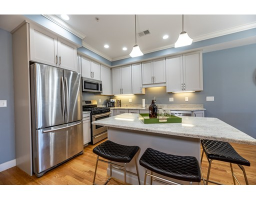 Belgrade Crossing is Commuter Convenience! This 2013 Bi-Level unit was built using the finest materials and highest quality standards and is mere steps to the train. Be in downtown in as little as 20 min.Amazing open concept floor plan that is defined by ceiling details and lighting. Custom Limestone kitchen cabinetry is topped with granite, stainless steel appliances, seating at the center island that is perfect for prep and conversation, crown, moldings, custom closets throughout, energy efficient multi-zone heating and cooling, on-demand tankless hot water, central vac, beautiful hardwood floors, in-unit laundry and so much more. Grill on your private roof deck, the gas grill is plumbed right in. Garage and Assigned Parking and Massive Private Storage Room!  The building is extremely well maintained and the association fee is very reasonable! Close to Roslindale Village with Farmer's Market and great dining options in the Village and along Centre St, Arboretum close.Truly Walkable!