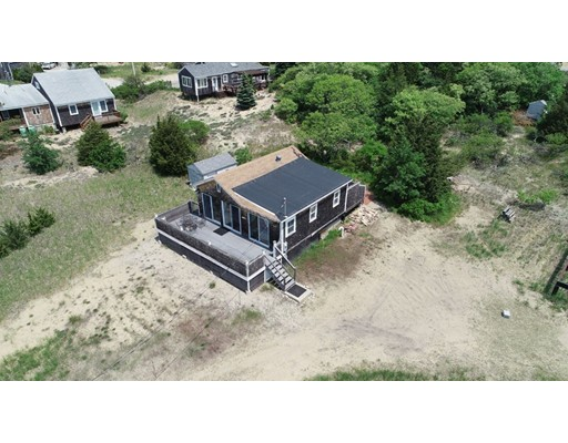 Salt air and Sunsets, Beach Cottage with strong rental history sits on a large 16,000 sq. ft. lot plus offering additional adjoined 5000 sq. ft. lot for 21,000 sq. ft. in total a 1/2 acre of land with views! Enjoy views of Newburyport city lights, the river and marsh throughout the seasons. Move in ready with huge decks to front and back for entertaining, outside shower and plenty of room to expand or just leave as your get away spot and the simple life. Come enjoy the Plum Island and Newburyport Lifestyle!