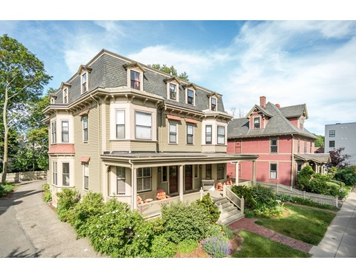 Few homes combine this level of sophisticated style & quality with an absolutely top location. Rarely available, 1,700+ sq ft condo situated on one of Jamaica Plain's foremost streets, Burroughs, & created in a stately Mansard Victorian. The home is comprised of three levels, boasting an enormous living & dining area with 11'+ ceilings, bow windows, a fireplace & astounding millwork, which prevails throughout the house. A spacious library/family room provides the perfect place to retire & is adorned with a window seat, decorative mantle, built-in book cases, & cornice cove moldings. Modern & sleek kitchen with a belly-up counter, & sitting area, which could serve as a 2nd dining area. Glass doors segue from here to a private deck, which also accesses the parking. The lower level offers additional 428 sq ft of finished space, bringing the usable square footage to 2,171. Location is a perfect balance; from artisan boutiques & shops of Centre St to the pastoral paths skirting Jamaica Pond