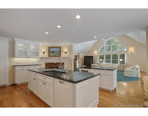 Spacious Contemporary Colonial set on a wonderfully private 4 plus acre lot with a natural wooded setting. Such a rare find to be so private and yet within walking distance to the Hamilton Wenham High School. The kitchen was recently transformed into a high end custom built chef's kitchen with double granite islands, high end stainless appliances, commercial grade gas stove, and a wood burning fireplace. The kitchen opens into an exceptionally large great room with high vaulted ceilings, perfect for large gatherings. The main living level also includes formal dining, a front to back living room with fireplace, study/office with fireplace and a private 3 seasons room. There are 5 fireplaces in total. The 5600 sqft of finished living offers 5 bedrooms on 3 living levels, each level with a full bath. Above the 3 car garage you will find a very spacious  bonus room or potential au-pair with custom shelving and additional storage.Recent gas conversion, updated system, central ac,new windows