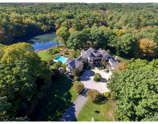 This Classic Shingle-Style Mansion, in Dedham's Precinct 1, provides a secluded 60 acre retreat with private pond within easy reach of Boston. Its foyer and spectacular three-story spiral staircase open on formal rooms, a library, a gallery, a guest suite and a stunning kitchen with a large fire-placed family room. Upstairs is a lovely master suite, a second laundry, five ensuite family bedrooms, a study area and a 2nd floor family room.  The ground floor has a wine cellar/ bar, billiards room, exercise room and a bath with steam and sauna, as well as a large theater and a large playroom. Outside you will find impressive landscaping and stone work with patios that overlook the pond, the infinity pool, the rolling lawns and the woods beyond. There is also a hockey rink with ice making and adjoining locker room, bathroom, garage and living room. The 60+ acres  has subdivision potential.  Ask the broker for details