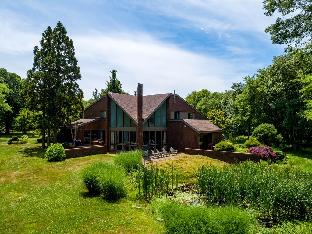 The desirable community of Shore Acres is the setting for this contemporary residence. The modern facade is unexpected, yet pleasing in this rural setting. Set back from the road, a winding paved driveway leads to the front door. Inside one is greeted with a sleek interior to include stone floors, floating stairs, a striking copper domed fireplace flanked by two walls of soaring windows, cozy alcoves and several options for dining including an outdoor patio accessible from both the kitchen and formal dining room. Up one short flight of stairs is a half level with a private one bedroom with ensuite bath.  Travel up another flight to find 3 additional bedrooms including a Master with ensuite bath and access to a secluded deck overlooking the home's extensive grounds. The finished basement can be used as a theater room, office or playroom.  While only minutes to Padanaram's Village and Harbor, this 2.5 acre property will surely serve as a haven for anyone seeking privacy.