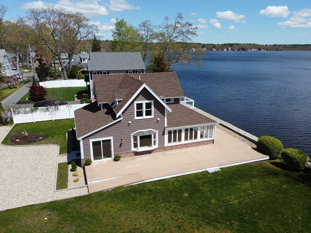 """You'll find respite at this peaceful """"waterfront"""" home in the private enclave of Historic Stony Point on Nelson's Grove. The views are amazing, capturing sunrise to sunset, overlooking the idyllic Lake Assawompset . Just under 2,000 sf, this craftsman style (completely re-built in 2021)  is truly a character home that welcomes you with unobstructed 180 degree water views from virtually every room. Sitting high on a knoll overlooking the lake, enjoy the outdoors on your private waterfront lot from your special spot on the sunny wrap-around mahogany deck or the 2nd floor balcony.  Features include a stone & cement breakwater barrier with its own unique slipway or landing projection, gourmet kitchen w/wet bar & island, reclaimed VT hdwd floors, optional 1st floor master & laundry, custom built-ins & high-end features such as professional stainless appliances & granite counters. Less than a one-hour commute to Boston, Providence & Cape Cod (close to commuter rail)"""