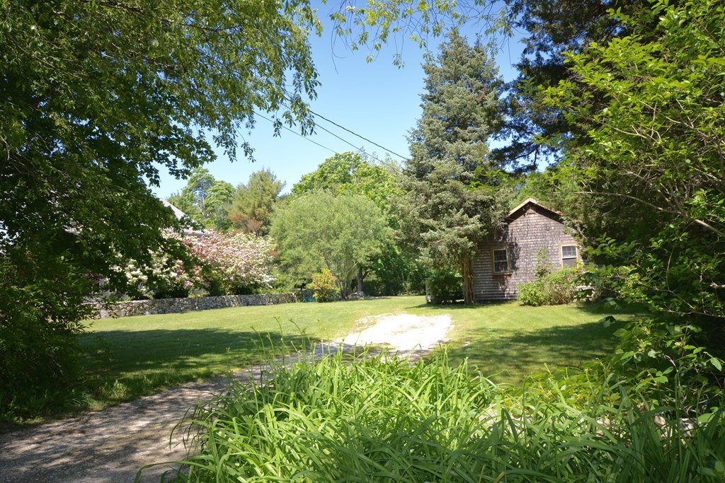 """Beautiful, prime building lot in East Fairhaven, bounded by stone walls on 3 sides, in residential neighborhood of substantial fine homes. Lot is approximately 30,000 sq ft with 100 ft of road frontage, clam shell driveway, established garden areas, giant oak tree ready for a swing, scores of high producing blueberry bushes and plenty of room for a pool. Included is the 1946 original cottage which could be improved, added onto or removed. Cottage has not changed much from when it was built and land has been in the same family since before World War II. High elevation with town sewer and natural gas already at street and close to Town bike path, accessed from neighboring street. Cottage currently served by Town water. Buyer responsible for tying into Town sewer. Selling """"AS IS"""", """" AS SEEN."""" All offers due by 5:00 PM June 23rd. Inspection for informational purposes only. First showing of cottage at Open House, Saturday, June 19th, 1-3:00 PM. Cash or conventional financing required."""