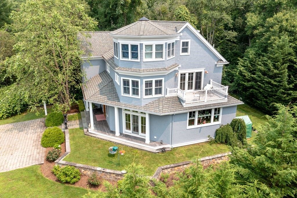 Mattapoisett village custom-built 4 BR, 5 BA, 3,236 sq ft home with deeded beach rights. Built in 2009, this property is just a few minutes' walk to Mattapoisett village, Shipyard Park, general store and Inn. Enjoy lazy days on a wrap-around porch or follow a narrow beach path to a private deeded beach overlooking Mattapoisett harbor. This open-concept home is built for entertaining with its vaulted great room, walls of windows, and chef's kitchen with Sub-Zero fridge, Wolf oven, custom cabinetry, and rear deck for outdoor grilling. With a primary bedroom on both the 1st and 2nd floors, every bedroom has its own ensuite bath. A 2nd floor balcony opens to the great room below and the staircase continues to the 3rd floor where a beautiful octagon room with vaulted mahogany bead-board ceiling offers views of Mattapoisett harbor and makes for the perfect home office. This home is filled with custom millwork inside while the pristine exterior was built for low maintenance living.