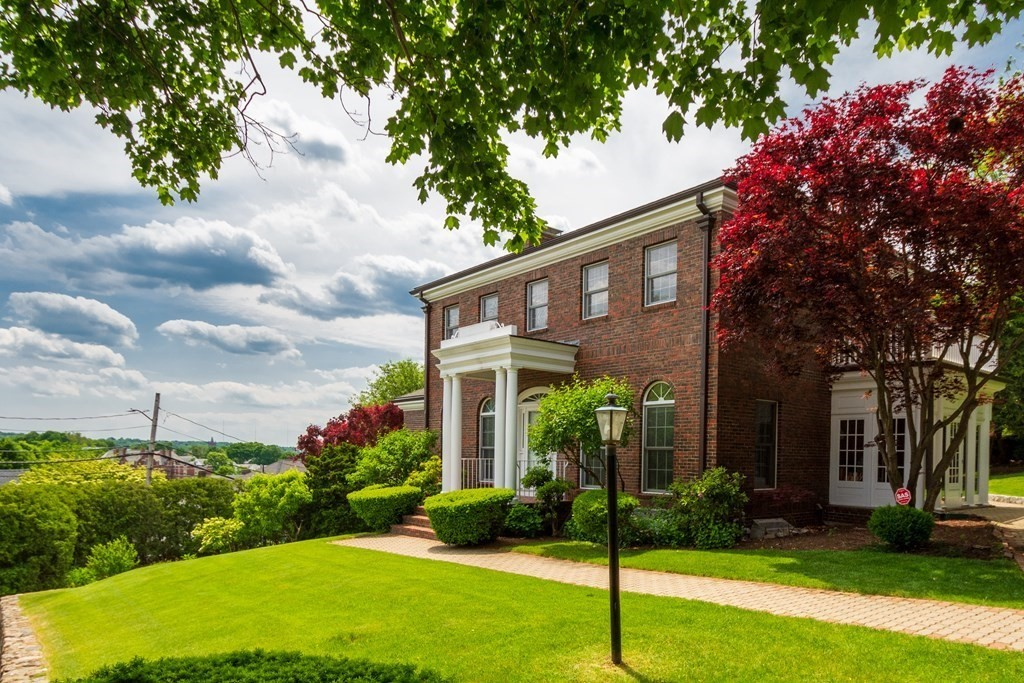 Gracious custom-built brick Georgian Colonial sits at the top of Watertown's great hill, abutting the Oakley Country Club, and offering unobstructed views of Boston's skyline. The grand foyer leads you into a sunlit home w/ a formal living room, dining room, eat-in kitchen, and three season porch on the 1st floor. The 2nd floor offers a front-to-back master bedroom suite w/ a full bath, private office, closet, and balcony.  There are two additional bedrooms and full bathroom on the 2nd floor. A staircase leads you to a walk-up attic w/ expansion potential. In the finished walk-out basement, there is a full in-law suite w/ a kitchen, bedroom, living room, and bathrooms. This one-of-a-kind property features hardwood floors, central air, custom built-ins, mudrooms, and more. Two paved driveways as well as a two-car garage! The private yard is surrounded by mature plantings. Walk to public transit, restaurants, Arsenal Yards and minutes to Cambridge/Boston.