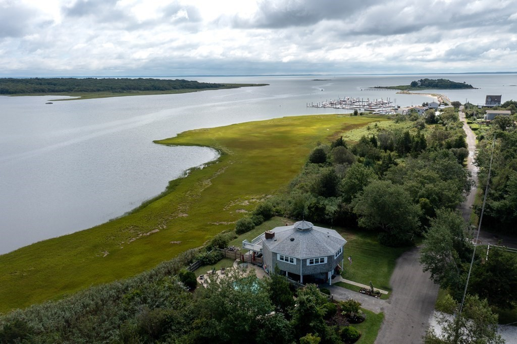 This 2BR/2BA Octagonal contemporary is situated on Brandt Island Cove w/ sweeping views of the marsh, ocean, and Brandt Cove Marina, in addition to looking East to Mattapoisett Neck w/ views of an array of migratory birds. The open-concept living space has a kitchen w/ a wall of windows and custom built cabinets, and living/dining room leading to an expansive deck on the South side of the home w/ some of the most breathtaking views you'll find in town. A naturally wooded yard flows to a fenced in yard with inground gunnite pool, garden and wood shed. There's ample storage under the house for kayaks, surf boards, etc. A new septic system is being engineered and will be installed. The roof is 6 years old and windows have been replaced. This property comes with an adjacent 10,137 SF water view lot presently deemed not buildable, which is included as a part of this sale. Both properties are in the Flood Zone. Buyers to do their due diligence as to the possibility of future town sewer.