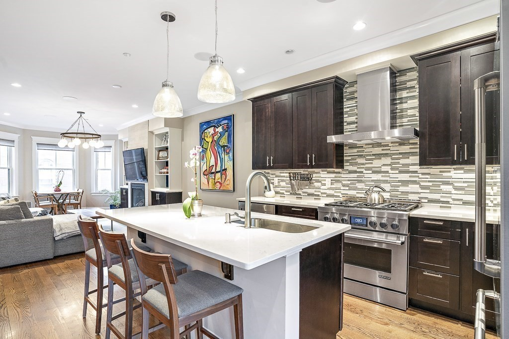 Don't miss this unique Townhome in S. Boston! It has the Trifecta- a quiet one way street on the coveted west side. A true neighborhood, including a new park 1 block away. With almost 2000sf interior space & over 1100sf of private outdoor space w/ spectacular views of the Boston Skyline, this property feels & lives like a single family!   1st floor offers an attached Garage, private entry, & private bedroom suite, perfect for in-laws/au pair/guests. 2nd floor is entirely open concept design w/ a suburban sized chef's kitchen featuring stainless appliances, gas cooking & 4-seat island. Large sunny dining area, powder room & comfortable living room w/ gas fireplace, built-ins & walk-out deck complete this floor. 3rd floor features laundry, guest room w/ en-suite bath and bedroom suite w/ marble bath, large walk-in closet & private deck. Top floor is ideal for a den or home office. Blocks to Seaport, Parks, Foodies & Green Line. Truly a masterpiece of design & location at a great price!