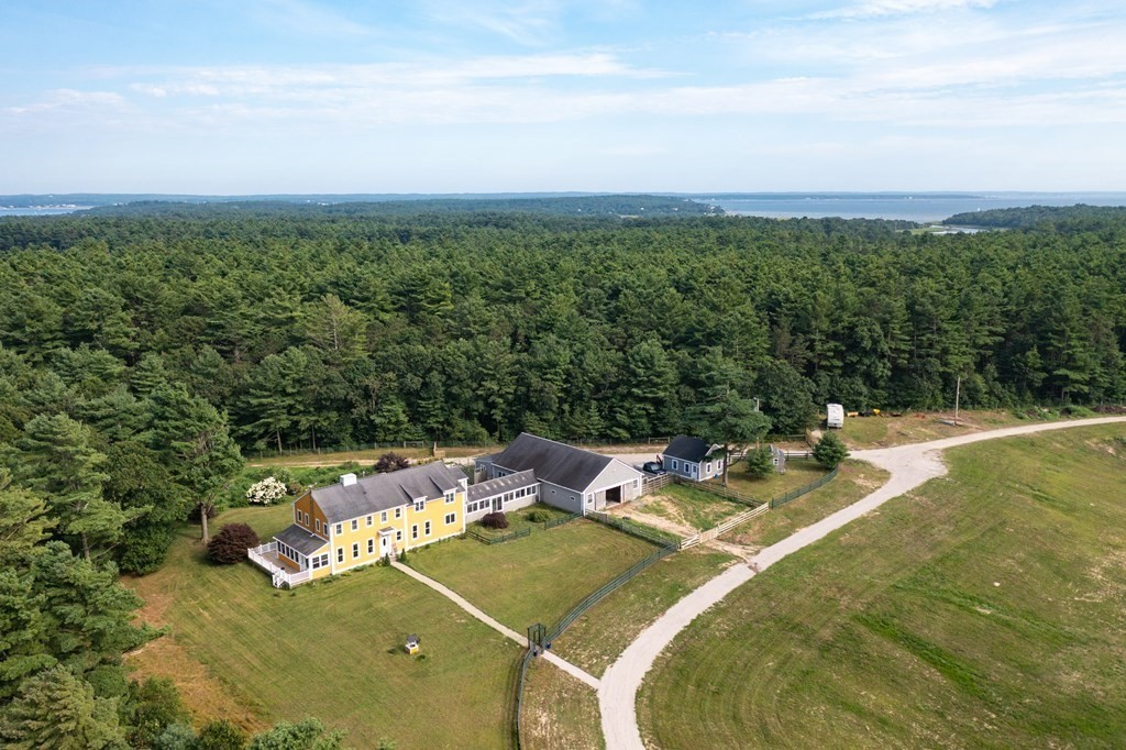 """Beautiful, gentleman's farm in the heart of coastal Wareham. Drive along a hidden lane to gates that open onto pastureland and wooded acreage and on to the striking farmhouse and outbuildings. Built in 2004, with poured concrete frame, this custom home is a modern interpretation of a New England """"L"""".The house is spacious with up to date amenities and finishes, offering a comfortable lifestyle with a nod to the area's history. Home to a small scale sheep farm for many years, the main pasture and house yard are fenced. The outbuildings include a free standing garage, 2 stall barn and outdoor pens. Additional farmhand apartment (one bedroom). Conservatory breezeway connects the main 2 car garage and house. The main level offers a living room, dining room and chef's kitchen with adjacent laundry room. First floor ensuite bedroom opens to an enclosed porch, deck and yard. Second floor features 2 ensuite bedrooms, a massive game room and bar,  and separate laundry facilities. Huge basement."""
