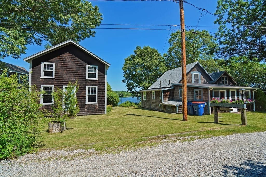 """RIVERFRONT SUMMER VACATION COTTAGE - Beautiful views of the east branch of the Westport River with access to a small beach and wooden deck overlooking the water.  Great place to launch a kayak or canoe.  Listen to the summer rain as it lands on the new roof (2018).  Three small bedrooms, one bath, hardwood floors, river view enclosed porch with many windows.  Excellent rental history.  Title V compliance will be Buyer's responsibility.  Huge storage shed/workshop on the property.  Community House and neighborhood tennis court nearby.  Land across the road (163 Cadmans Neck Road) is included in the sale.  Cottage dates back to the days of Cadmans Neck """"Camp Meetings"""" and is being sold """"As-Is"""".  A very charming and cozy summer cottage from yesteryear!"""