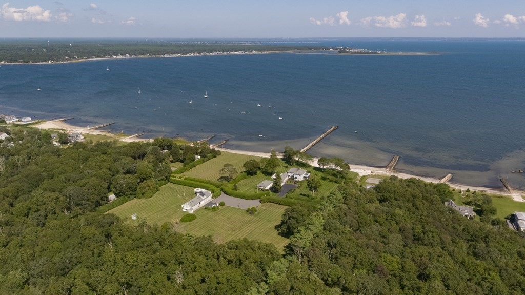 Quintessential New England waterfront home perfectly situated on almost 6 acres, nestled on Mattapoisett Harbor. Almost 300' of private beach frontage with multiple mooring opportunities and direct access to Buzzards Bay with no bridge traffic. This estate has been family-owned for over 80 yrs and includes a separate guest house with its own garage and deck with water views. The main house boasts 4 bedrooms, 3 full & 2 half baths. Stunning water views from the picture windows in the living room, upstairs bedrooms and generous outdoor patio. Spacious play room with plenty of space for ping pong, lounging and pool. Oversized, multiple-car garage and plenty of outdoor parking. This home has been lovingly and meticulously cared for throughout generations. The manicured grounds are completely private with lush landscaping and expansive side yards, perfect for outdoor summer entertaining. Enjoy fishing off the approximately 500' pier, swimming and all types of boating. Unique opportunity.