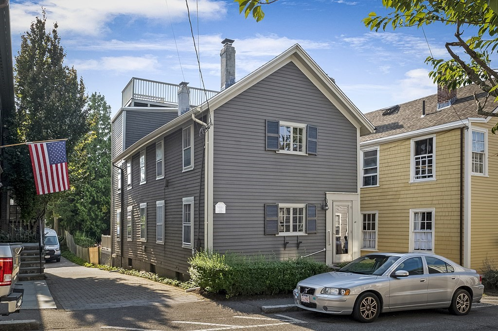 """Downtown """"Old town"""" this 1856 3 plus bedroom 1.5 bath Colonial is steps to the harbor, Crosby's Market, The Landing/Barnicle Restaurants and all the shops and charm of Historic Marblehead. Parking to the right of the front door for 1 plus cars. Recent improvements include: new asphalt roofing.(Old asphalt stripped); Left and rear side of exterior prepped and newly painted; Newer domestic high efficient hot water system. Open, sunny and bright, period flooring and 1 wood burning fireplace. Front and rear interior staircases offer flexible living. Open finished 3rd level room for 4th bedroom or great office with peeks of the harbor. Access to rooftop deck with panoramic views  of Marblehead Harbor and beyond. Lovely level rear yard/gardens, patio and raised terrace. Property sold in """"as is """" condition. Price is accounting for improvement opportunities that include HVAC, kitchen, baths etc. Location! Location!! Please allow 24 hours for offer. response. Thank you."""