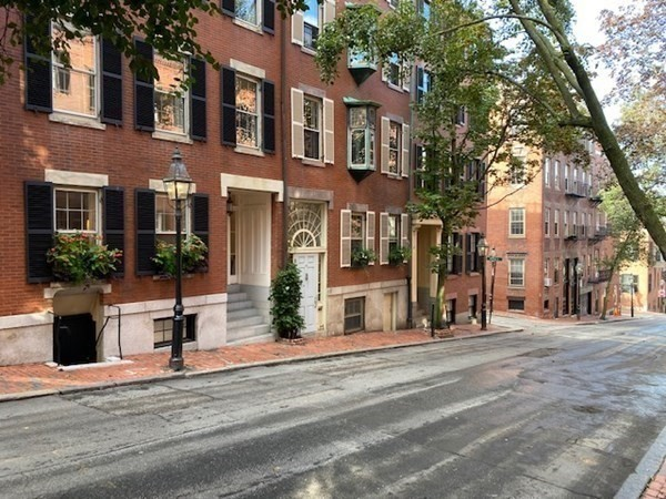 Amid the picturesque charm of historic Beacon Hill, in a quiet setting just off Charles Street, this circa 1855 Federal-style townhouse has been beautifully renovated with a versatile, refined look and a flexible layout providing wonderful spaces for modern-day living and entertaining. The tastefully designed 4-bedroom home reflects timeless style, and the view from every window is a quintessential Beacon Hill vignette. Featuring 2 fireplaces, the expansive full-floor open living/dining room is lined with built-ins including a wet bar. Another wet bar serves the family room, open to the garden level's airy 2-story casual dining room with French limestone floors and French doors to an inviting courtyard terrace with fountain. The chef's kitchen centers on a professional-grade Lacanche range. The primary bedroom suite features a closet-lined dressing room and luxurious marble bath, with a bedroom/office/gym across the hall. A private deck and media/play room are on the upper levels